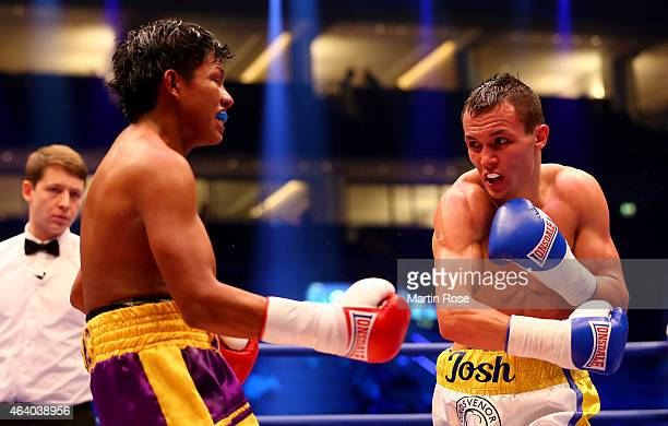 Edwin Tellez of Nicaragua exchange punches with Josh Warrington of Great Britain during their feather weight fight at o2 World on February 21 2015 in...