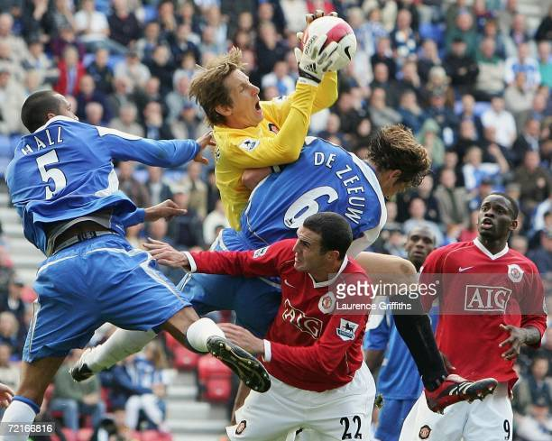 Edwin Van Der Sar of Manchester United collects the ball in front of John O'Shea under pressure from Fitz Hall and Arjan De Zeeuw of Wigan during the...
