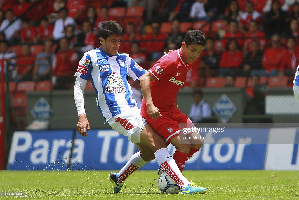 Edy Brambilla (L) of Toluca struggles for the ball with Richard Ortiz (R) of Tijuana during the match between Toluca and Pachuca as part of the Apertura 2013 Liga Bancomer MX at Nemesio Diez Stadium on july 21, 2013 in Toluca, Mexico.