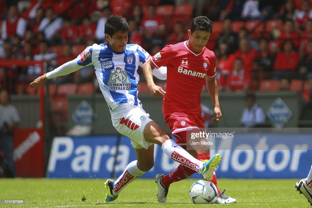 Edy Brambilla of Toluca struggles for the ball with Richard Ortiz (L) of Tijuana during the match between Toluca and Pachuca as part of the Apertura 2013 Liga Bancomer MX at Nemesio Diez Stadium on july 21, 2013 in Toluca, Mexico.