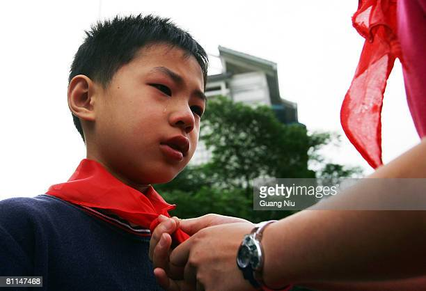 Eearthquake survivor student Yang Like is given a red scarf as he is welcomed to Chengdu Jiaozi School as China begins three days of national...