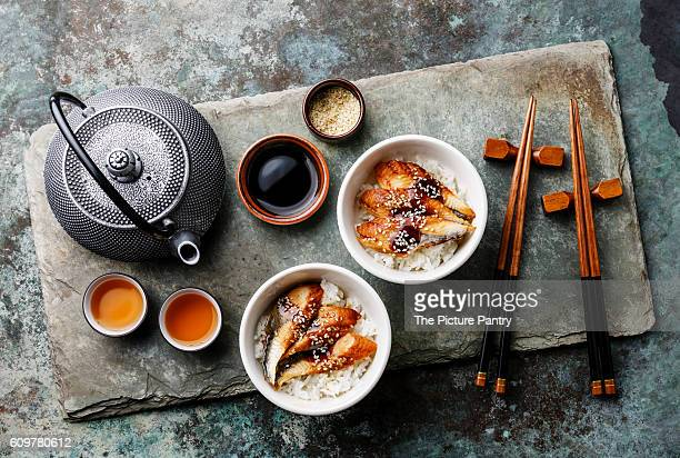 Eel on Rice with sauce and sesame for two on stone slate background and tea