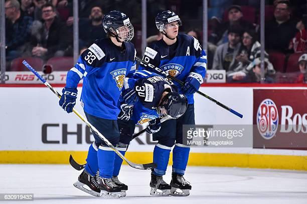 Eeli Tolvanen and Vili Saarijarvi of Team Finland carry out teammate Kristian Vesalainen during the 2017 IIHF World Junior Championship relegation...