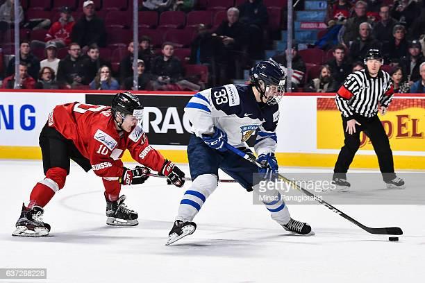 Eeli Tolvanen of Team Finland skates the puck against Serge Weber of Team Switzerland during the 2017 IIHF World Junior Championship preliminary...