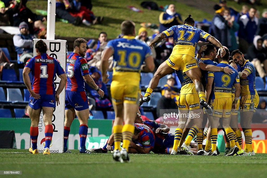 Eels team mates celebrate a try with Knights looking dejected during the round 12 NRL match between the Newcastle Knights and the Parramatta Eels at Hunter Stadium on May 30, 2016 in Newcastle, Australia.