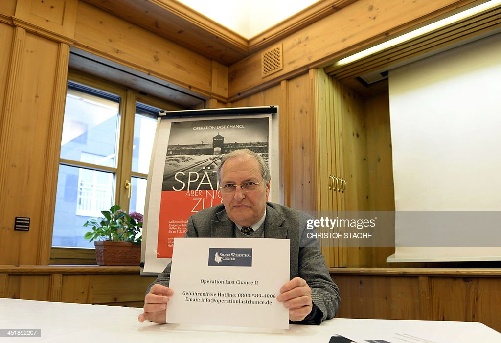 Efraim Zuroff, director of the Jerusalem Office of the Simon Wiesenthal Center, displays a hotline number ahead a news conference on the center's initiative 'Operation last chance - late but not too late' in Munich, southern Germany, on November 25, 2013. Efraim Zuroff launched the 'Operation Last Chance II', a campaign to bring individuals to justice who were involved in the mass murder of Jews during the Holocaust. With 2,500 placards in the German cities of Munich, Leipzig, Dresden, Magdeburg, Rostock, Stuttgart, Nuremberg and Frankfurt, the Simon Wiesenthal Center re-launched the campaign to find and prosecute Nazi war criminals who are still alive.