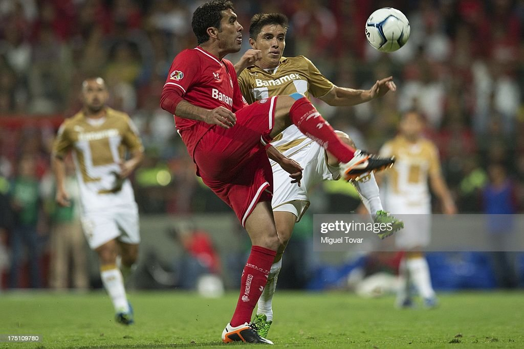 Efrain Velarde of Pumas fights for the ball with Edgar Due–as of Toluca during a match between Toluca and Pumas as part of the Torneo Apertura 2013 Liga MX at Nemesio Siez stadium, on July 31, 2013 in Toluca, Mexico.