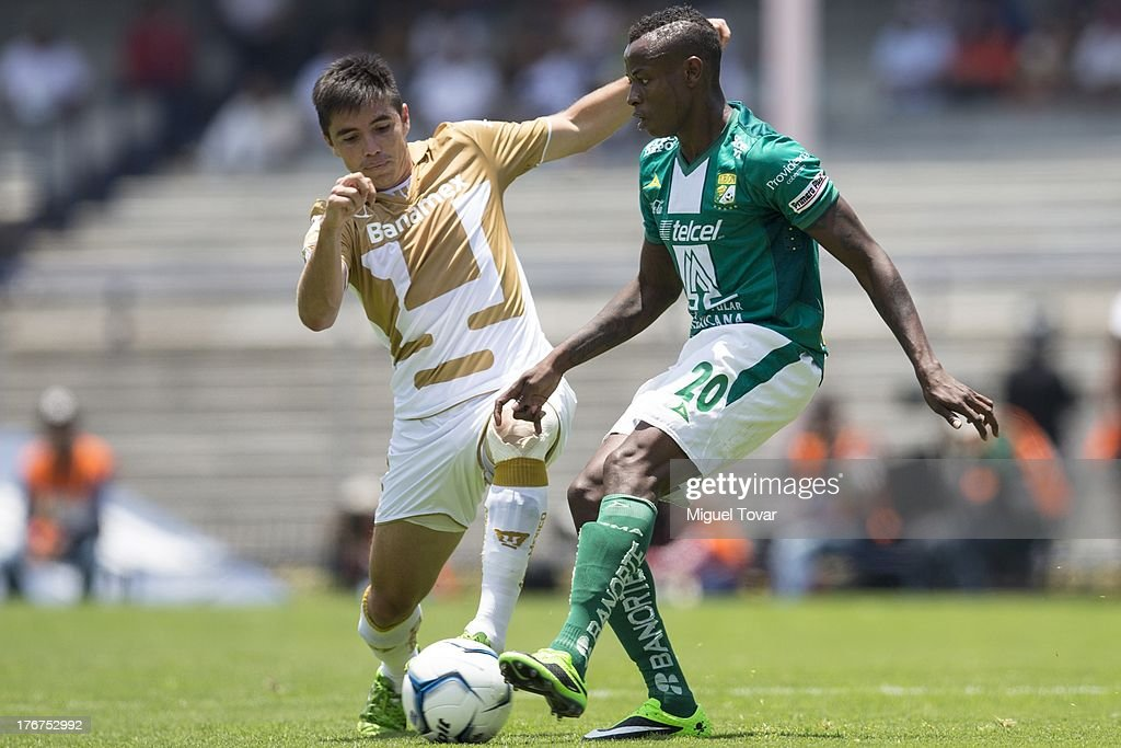 Efrain Velarde of Pumas fights for the ball with Eisner Loboa of Leon during a match between Pumas and Leon as part of the Apertura 2013 Liga MX at Olympic stadium, on August 18, 2013 in Mexico City, Mexico.