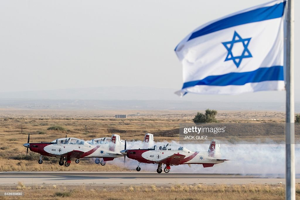 Efroni T-6 Texan II planes perform in an air show during the graduation ceremony of Israeli air force pilots at the Hatzerim base in the Negev desert, near the southern Israeli city of Beer Sheva, on June 30, 2016. / AFP / JACK