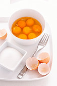 Egg yolks and egg whites in bowl, with eggshells, fork and sugar bowl on tray, close-up
