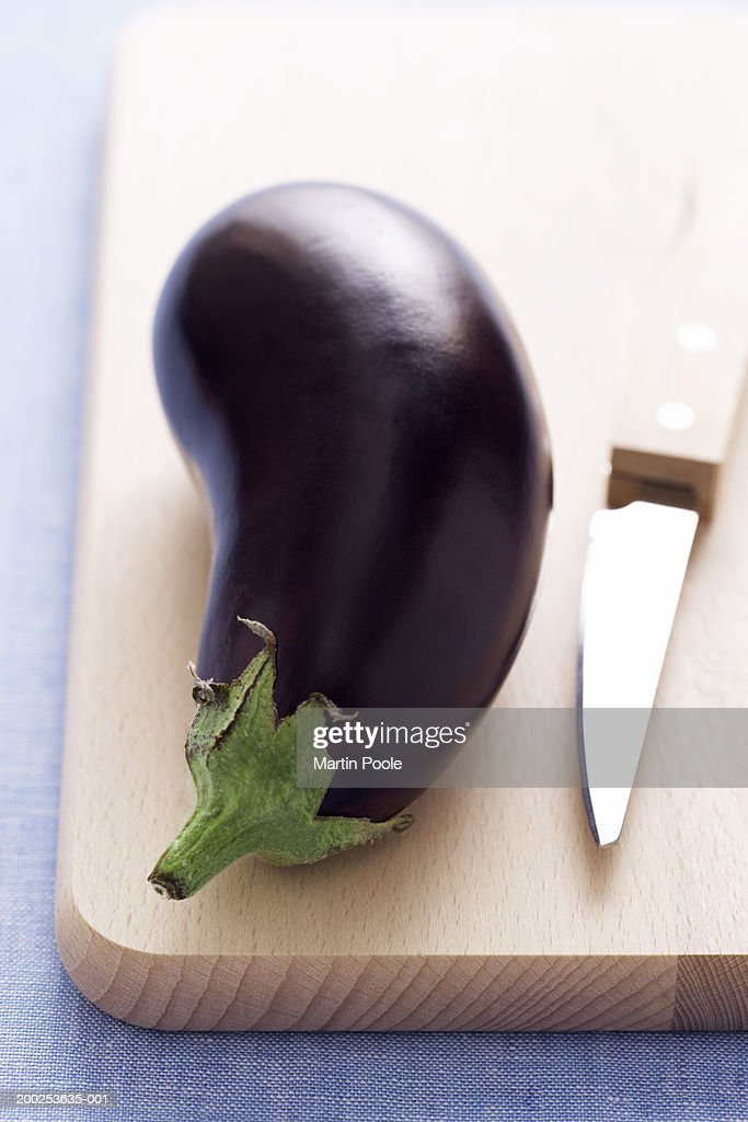 Eggplant and knife on wooden chopping board, close-up : Stock Photo