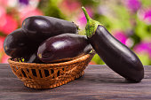 eggplant in a wicker basket on a wooden table with a blurred background.