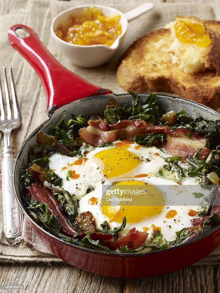 Eggs, dandelion greens and bacon in a  skillet : Stock Photo