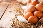 Eggs in a heap of Hay on wooden table