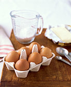 Eggs in carton with butter and flour