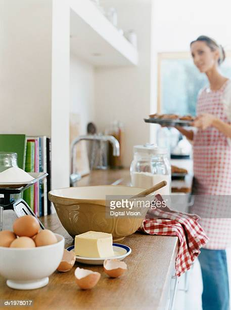 Eggs, Kitchen Scales, Butter and a Bowl With Spoon on Kitchen Counter, Woman Holding a Baking Tray on Background