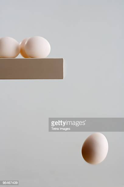 Eggs on ledge with one falling