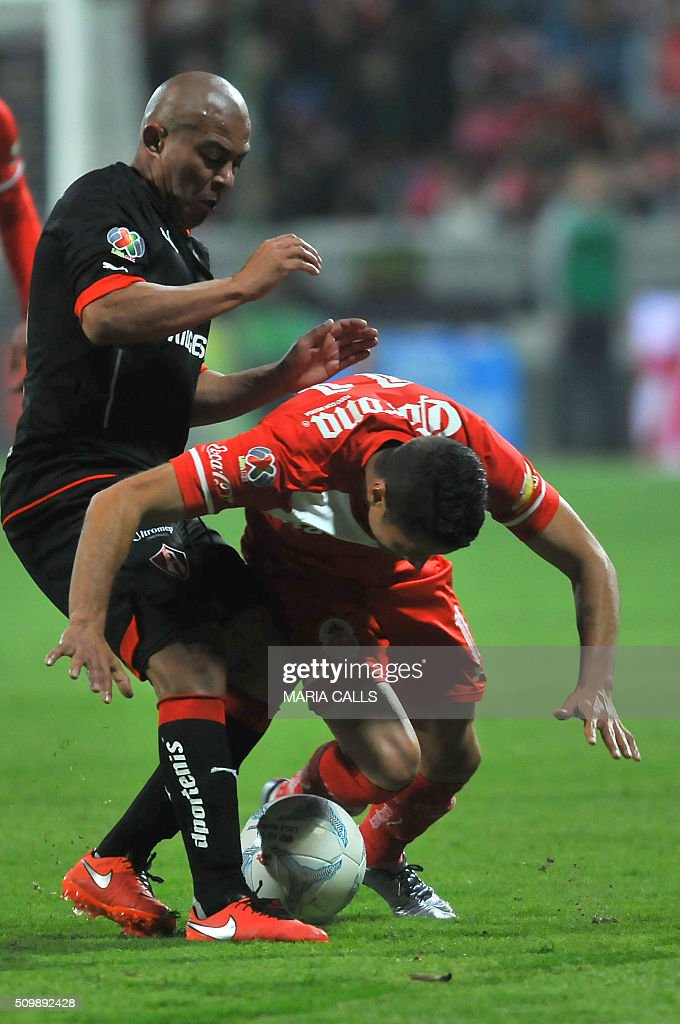 Egidio Arevalo (L) of Atlas vies for the ball with Carlos Esquivel of Toluca during the Mexican Clausura 2016 Tournament at the Nemesio Diez stadium on February 12, 2016, in Toluca ,Mexico. / AFP / MARIA CALLS