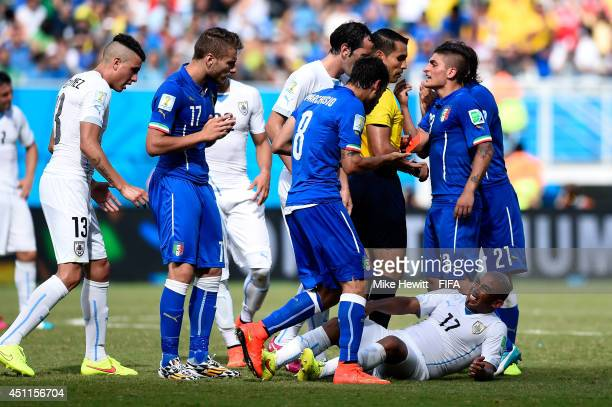 Egidio Arevalo Rios of Uruguay lies injured prior to Claudio Marchisio of Italy being shown a red card during the 2014 FIFA World Cup Brazil Group D...