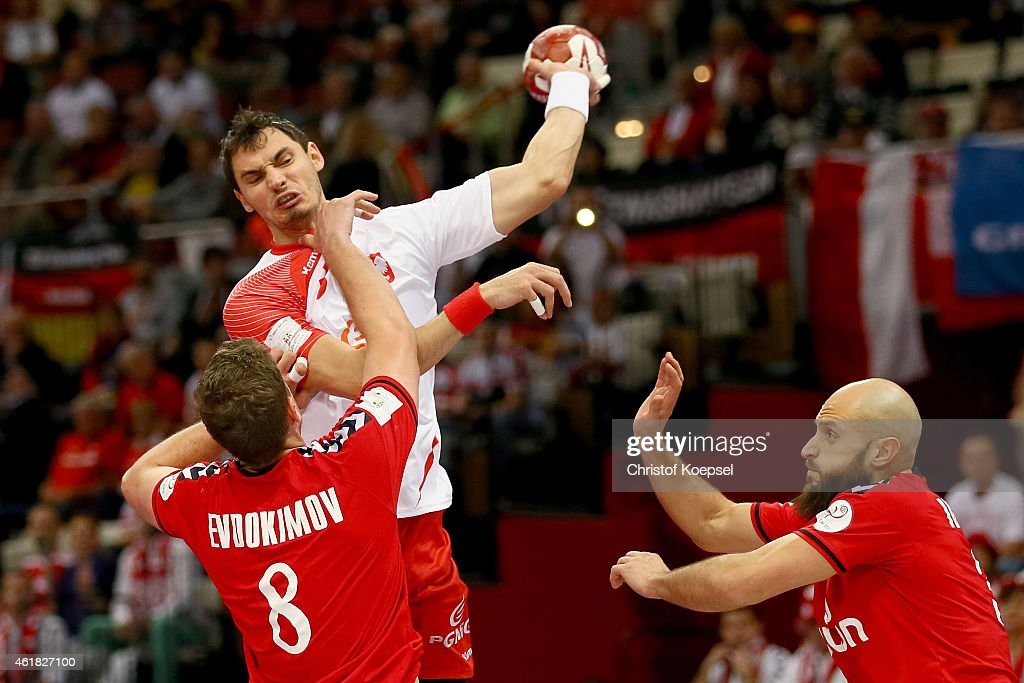 Egor Evdokimov of Russia (L) and Timur Dibirov of Russia (R) defend against Krzystof Lijewski of Poland (C) during the IHF Men's Handball World Championship group D match between Poland and Russia at Lusail Multipurpose Hall on January 20, 2015 in Doha, Qatar.