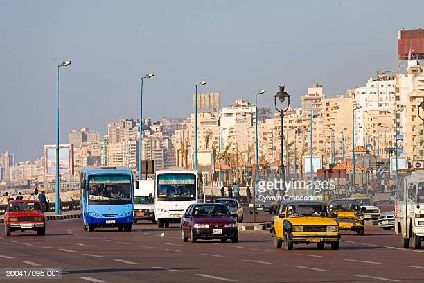 Egypt, Alexandria, cars driving down street with skyline behind