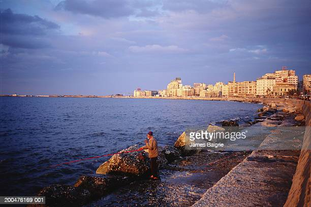 Egypt, Alexandria, senior man fishing, sunset