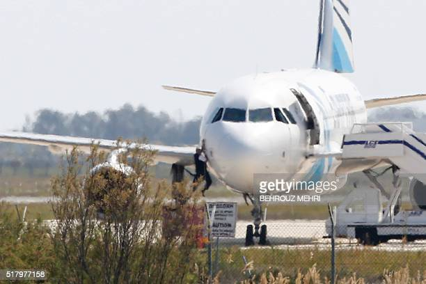TOPSHOT EgyptAir copilot Hamad elKaddah climbs out of the cockpit window of an EgyptAir Airbus A320 parked at the tarmac of Larnaca airport after...