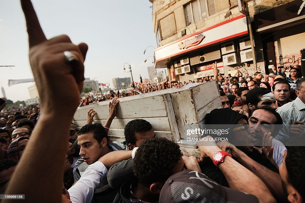 Egyptian Activists and April 6 movement members carry the coffin of Gaber Salah, an activist who died overnight after he was critically injured in clashes near Cairo's Tahrir Square last week, during his funeral at Tahrir square on November 26, 2012 in Cairo. Salah, a member of the April 6 movement known by his nickname 'Jika', was hurt in confrontations between police and protesters on Mohammed Mahmud street where protesters had been marking the first anniversary of deadly clashes.
