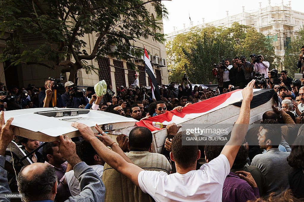 Egyptian Activists and April 6 movement members lift the coffin of Gaber Salah, an activist who died overnight after he was critically injured in clashes near Cairo's Tahrir Square last week, during his funeral at Tahrir square on November 26, 2012 in Cairo. Salah, a member of the April 6 movement known by his nickname 'Jika', was hurt in confrontations between police and protesters on Mohammed Mahmud street where protesters had been marking the first anniversary of deadly clashes.