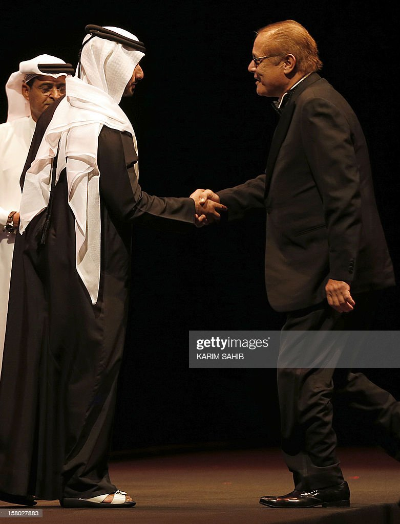 Egyptian actor Mahmud Abdel Aziz (R) receives an IWC watch, as part of the Lifetime Achievement award presentated by Sheikh Mansur bin Mohammed bin Rashid al-Maktoum (L) at the Dubai International Film Festival in the Gulf emirate of Dubai, on December 9, 2012. AFP PHOTO/KARIM SAHIB