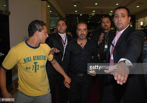 Egyptian actor Mohammad Saad is flanked by bodyguards upon his arrival at a movie theatre in Cairo to attend the premiere of his new film 'Cabaret'...