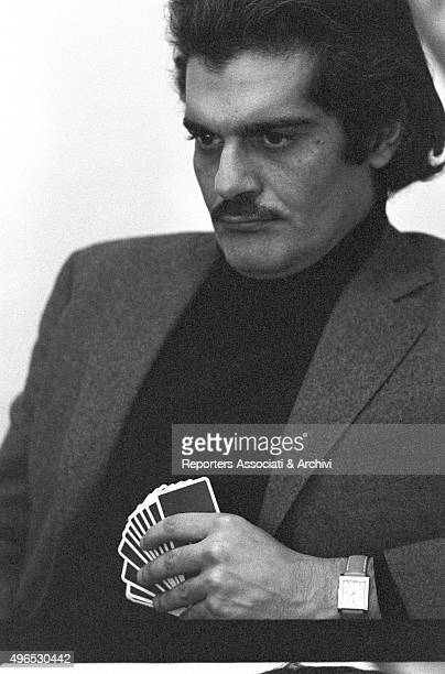 Egyptian actor Omar Sharif known for being a great bridge player playing cards in the foyer of a theatre 1968