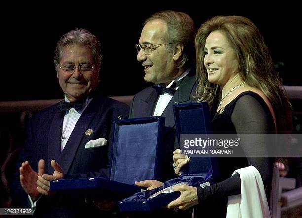 Egyptian actress Najlaa Fathi and actor Mahmoud Yassin receive their honorary award during the opening ceremony of Cairo's 24th International Film...