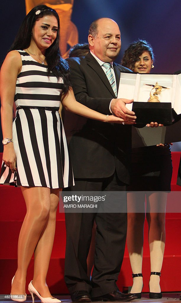 Egyptian actress Rania Youssef (L) receives the best actress award from Egyptian Minister of Culture Mohamed Saber Arab (C) for her role in the film 'One who's True' during the closing ceremony of the 17th National Festival of Egyptian Cinema on November 26, 2013.