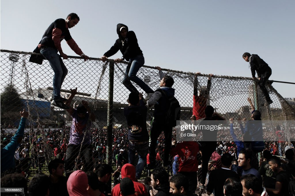 Egyptian 'Ahly Ultra' soccer fans climb over a fence at the Al Ahly home stadium during celebrations after the announcement that 21 fans of the Al Masry football club involved in a football stadium massacre last year were sentence to death on January 26, 2013 in Cairo, Egypt. A verdict was announced Saturday in a case over the deaths of more than seventy fans of Egypt's Al-Ahly football club in a stadium massacre on February 1, 2012, in the northern city of Port Said, during a riot that began minutes after the final whistle of a match between Al-Ahly and Al-Masry. 21 fans of the Al Masry football club were given the death penalty in the court case, a verdict that must now be approved by Egypt's Grand Mufti. The verdict was handed down during a period of high tension across Egypt, one day after the second anniversary of the beginning of Egypt's 2011 revolution that overthrew the regime of former President, Hosni Mubarak.