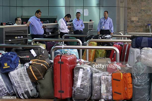 Egyptian airport staff stand next to the luggage at the departure terminal in Egypt's Red Sea resort of Sharm ElSheikh on November 5 2015 Britain and...