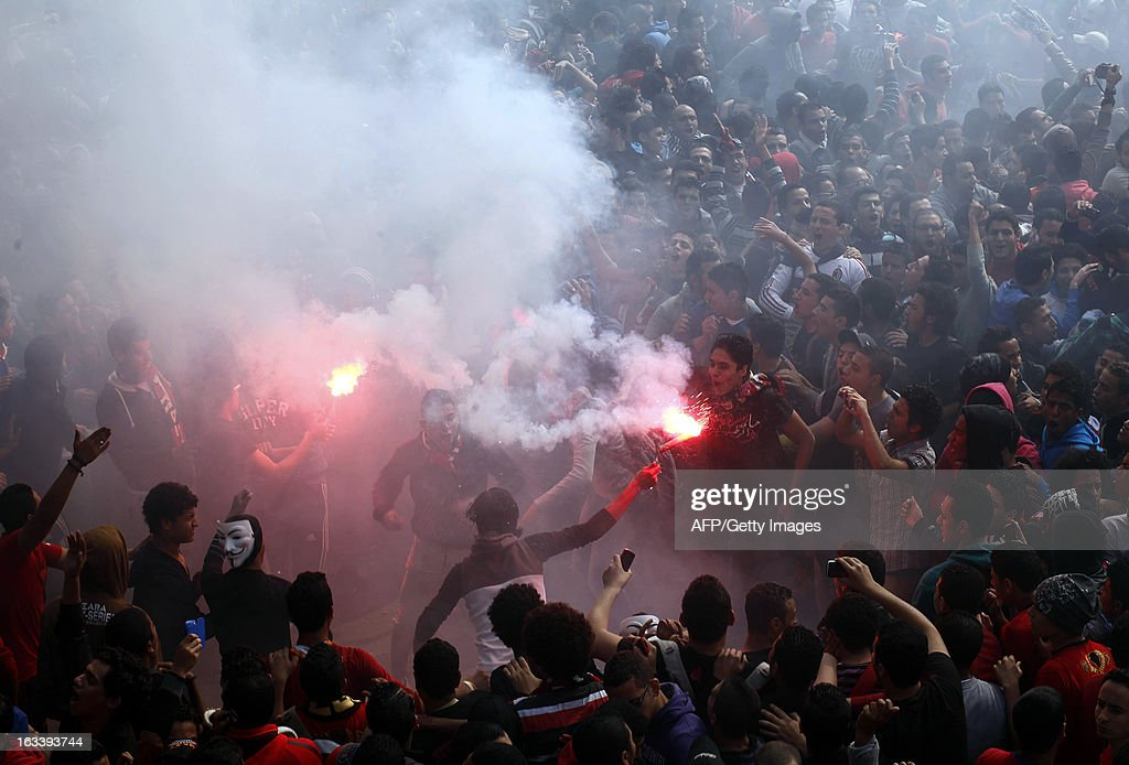 Egyptian al-Ahly football club supporters (Ultras) light flares as they celebrate in Cairo on March 9, 2013, after an Egyptian court upheld death sentences for 21 defendants over a deadly football riot in Port Said that killed 74 people last year. The court, sitting in Cairo for security reasons, also handed down life sentences to five defendants, with 19 receiving lesser jail terms and another 28 exonerated. AFP PHOTO / MAHMUD KHALED