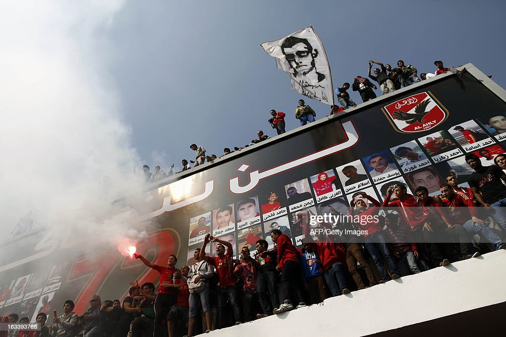 Egyptian al-Ahly football club supporters (Ultras) stand in front of a poster of portraits of the victims from the deadly football riot in Port Said that killed 74 people last year, as they celebrate in Cairo on March 9, 2013, after an Egyptian court upheld death sentences for 21 defendants over the clashes. The court, sitting in Cairo for security reasons, also handed down life sentences to five defendants, with 19 receiving lesser jail terms and another 28 exonerated. AFP PHOTO / MAHMUD KHALED
