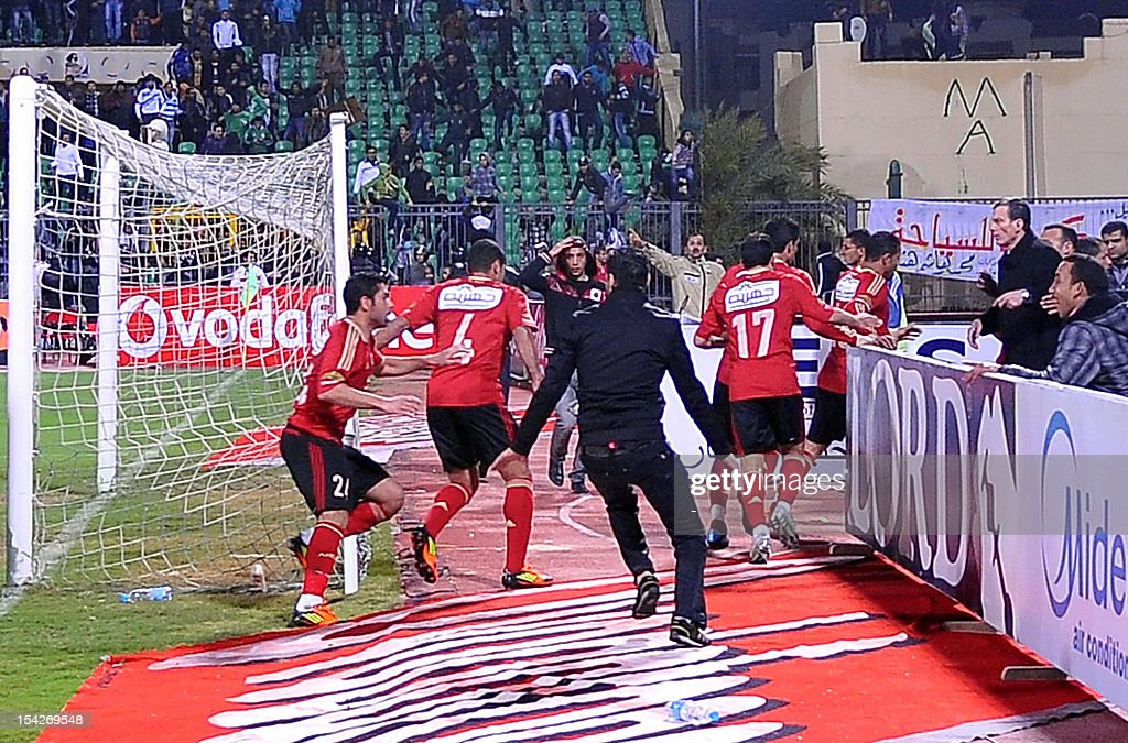 Egyptian AlAhly players escape from the field as fans of AlMasry team rush after them during riots that erupted after the football match between the...