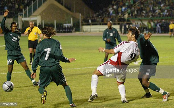 Egyptian and Libyan players fight for the ball during a 2006 World Cup qualifying match for the group three in Cairo 27 March 2005 AFP PHOTO/SAMEH...