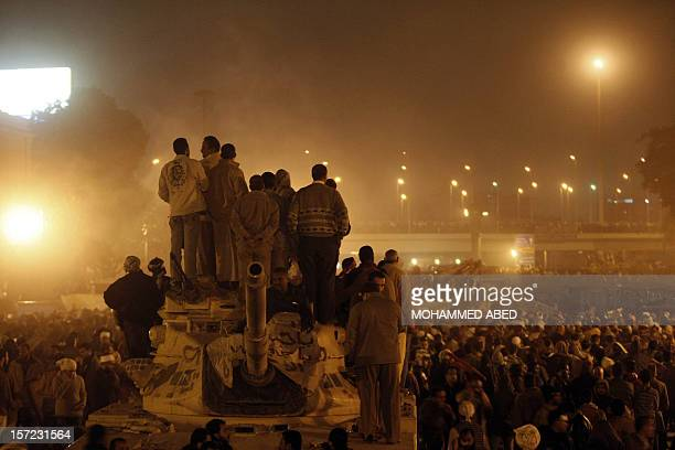 Egyptian antigovernment demonstrators stand on an Egyptian army tank at during a protest calling for the ouster of President Hosni Mubarak at Cairo's...