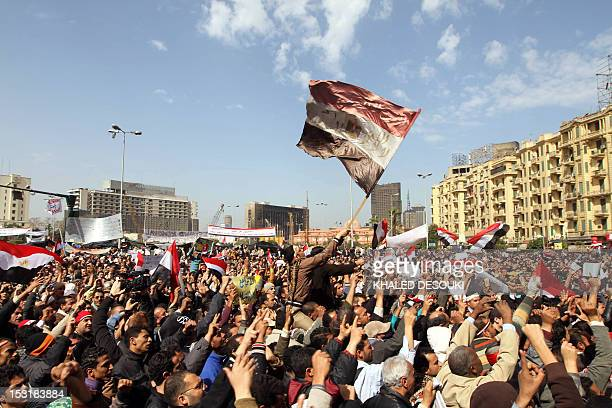 Egyptian antigovernment demonstrators wave their national flag as they gather at Cairo's Tahrir Square on February 6 2011 on the 13th day of protests...