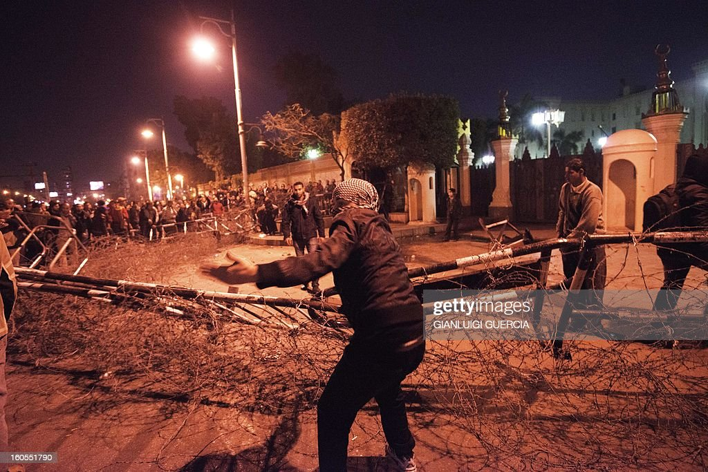 Egyptian anti-government protesters pull off barbed wire barricades from one of the main gate of the Presidential Palace during a demonstration on February 2, 2013 in Cairo. Egypt's main opposition group on Saturday backed calls to oust the ruling Islamists after deadly clashes and as President Mohamed Morsi scrambled to contain fallout from footage of apparent police brutality. GUERCIA