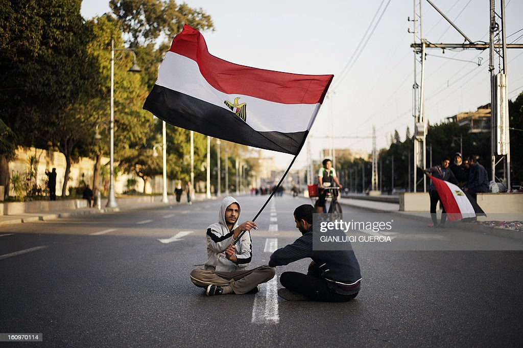 Egyptian anti-government protesters sit waving their national flag outside the Egyptian presidential palace in Cairo during a demonstration against Egypt's President Mohamed Morsi and the Muslim Brotherhood on February 8, 2013. Thousands took to the streets across Egypt after opposition groups called for 'Friday of dignity' rallies demanding Morsi fulfill the goals of the revolt that brought him to power. AFP PHOTO/GIANLUIGI GUERCIA