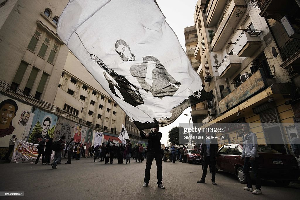 Egyptian anti-government protesters wave a giant flag featuring a protester who died during last week's demonstrations against Morsi and his Muslim Brotherhood on February 7, 2013 in the city center of the Egyptian capital Cairo. The 23-year-old man, Mohammed Hussein Qarni died of a gunshot wound outside the presidential palace on February 1, where stone and petrol bomb throwing protesters faced off with police into the night.