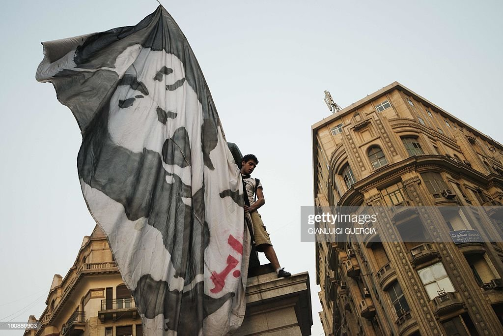 Egyptian anti-government protesters wave a giant flag featuring a protester who died during last week's demonstrations against Morsi and his Muslim Brotherhood on February 7, 2013 in the city center of the Egyptian capital Cairo. The 23-year-old man, Mohammed Hussein Qarni died of a gunshot wound outside the presidential palace on February 1, where stone and petrol bomb throwing protesters faced off with police into the night. AFP PHOTO/GIANLUIGI GUERCIA