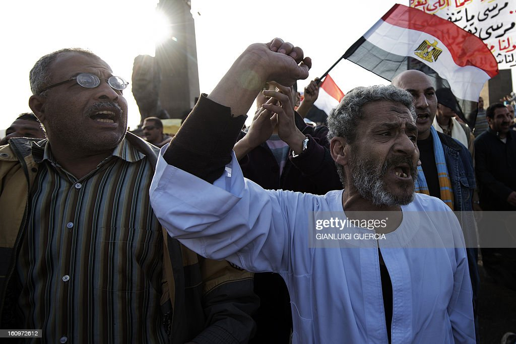 Egyptian anti-government protestors shout political slogans as they wave their national flag and banners during a march towards Cairo's landmark Tahrir square during a demonstration against Egypt's President Mohamed Morsi and the Muslim Brotherhood on February 8, 2013. Thousands took to the streets across Egypt after opposition groups called for 'Friday of dignity' rallies demanding Morsi fulfill the goals of the revolt that brought him to power.