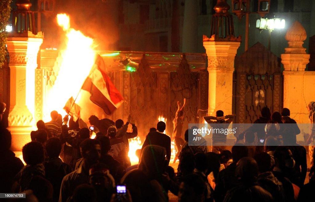 Egyptian anti-regime protesters set fire to the gate of the presidential palace during a demonstration in Cairo on February 8, 2013. Egyptian police fired tear gas at protesters who lobbed petrol bombs and set off fireworks outside the presidential palace, amid nationwide rallies against President Mohamed Morsi. AFP PHOTO / AHMED MAHMOUD