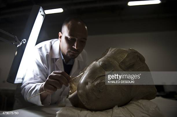 Egyptian archaeologist Basem Gehad cleans a pharaoh's head at the Grand Egyptian Museum still under construction near the Giza pyramids in Cairo on...