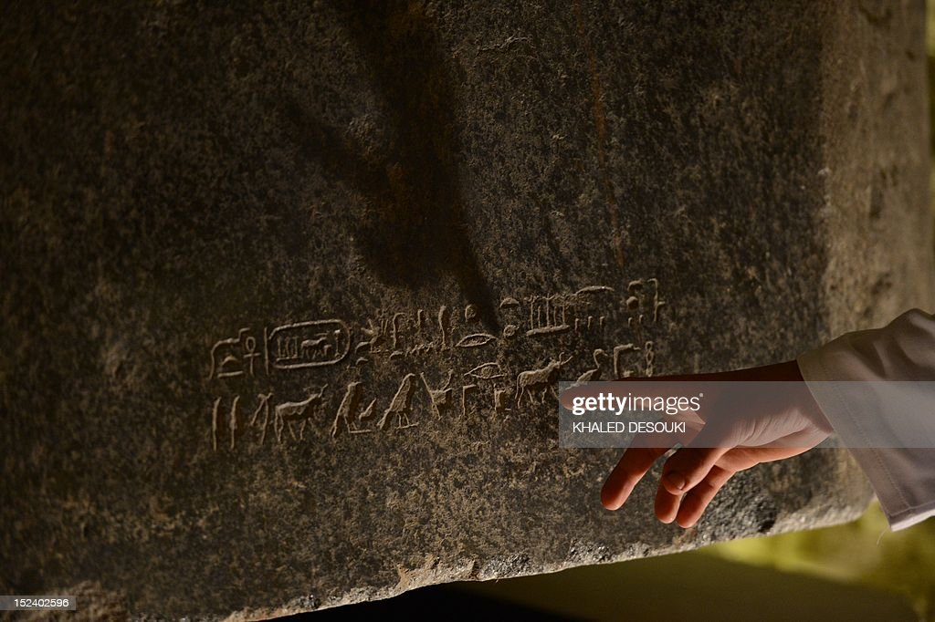 Egyptian archeologist Mohamed Abdelsatar, displays an inscription on a tomb at the Serapeum of Saqqara, a vast underground necropolis south of Cairo dedicated to the bulls of Apis, as it reopens to the public after 11 years of renovation, on September 20, 2012 . The Serapeum, whose origin dates back to around 1400 BC, was discovered in 1851 by French Egyptologist Auguste Mariette, founder of the first department of Egyptian antiquities. The site contains huge subterranean galleries in which are contained the large tombs of some 30 sacred bulls, accompanied by steles bearing inscriptions providing information on the reigns under which the animals lived.